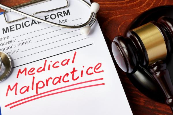medical malpractice written in red ink on a medical form with a judg'es gavel next to the form